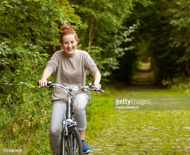 meisje dat een fiets in openlucht op een open vlek in het hout berijdt - buitensport stockfoto's en -beelden