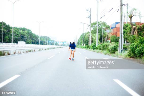 a girl riding a skateboard - yusuke nishizawa stock pictures, royalty-free photos & images
