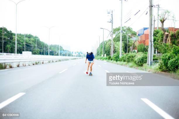 a girl riding a skateboard - yusuke nishizawa stock-fotos und bilder