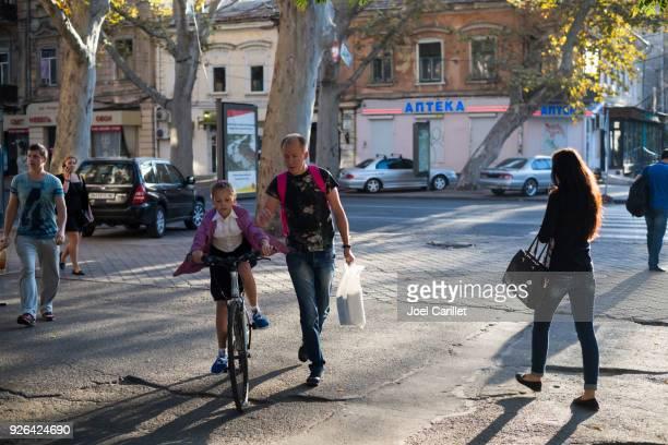 girl riding back to school in odessa, ukraine - odessa ukraine stock photos and pictures