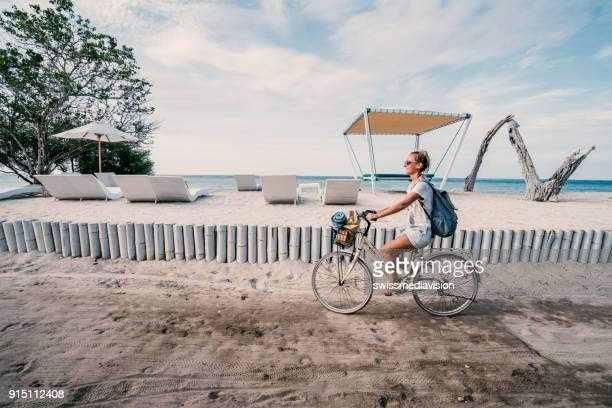 girl riding bicycle by the beach in the morning, indonesia - gili trawangan stock photos and pictures