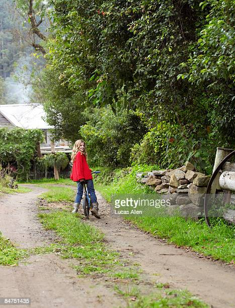 Girl riding bicycle down country driveway