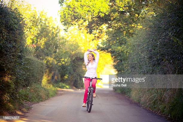 Girl riding bicycle in country road in the summer.