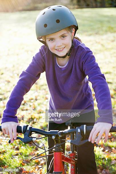 Girl riding bicycle in meadow