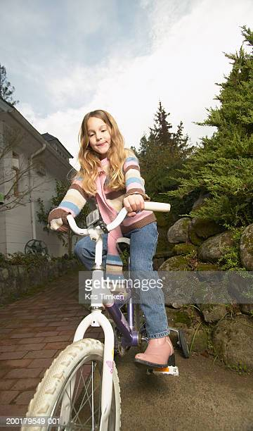 Girl (5-7) riding bicycle, low angle view