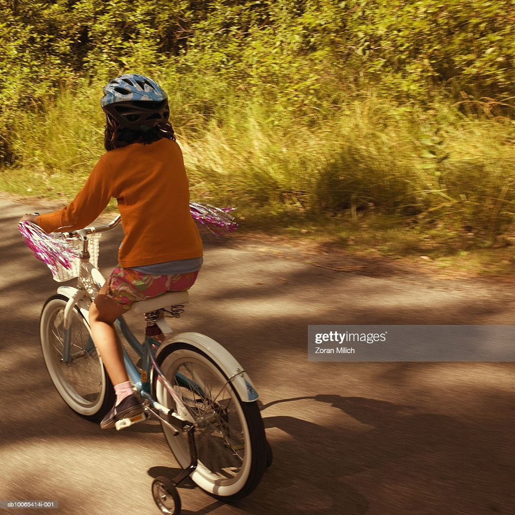 Girl (8-9) riding bicycle on road : Foto stock