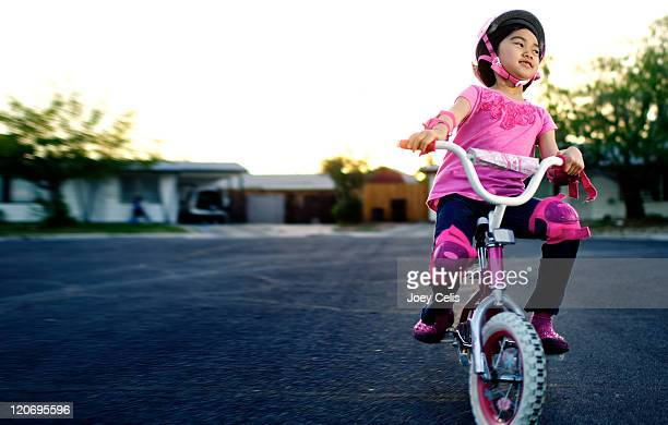 girl riding bicycle on street - las vegas girls stock photos and pictures