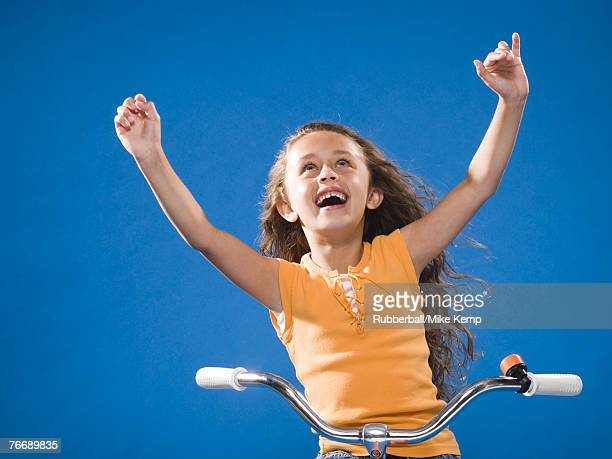 girl riding bicycle with no hands smiling - hands free cycling stock pictures, royalty-free photos & images
