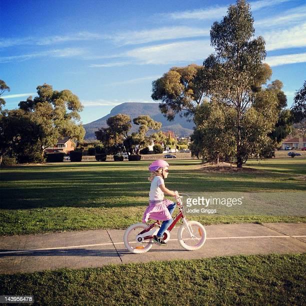 Girl riding bike along path