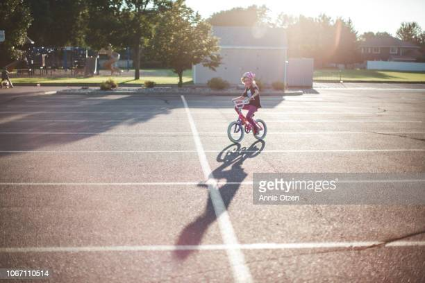 girl riding bike in empty parking lot - bicycle parking station stock photos and pictures