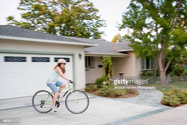 Girl Riding Bike in Front of House