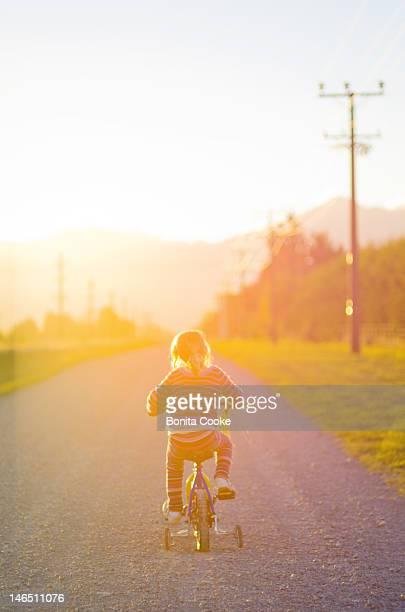 Girl riding bike on dirt road