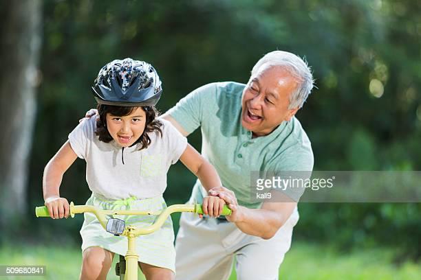 Girl riding bike, with grandfather