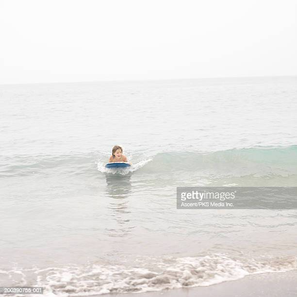 Girl (9-11) riding body board on wave