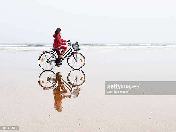 Girl riding bycicle at the beach