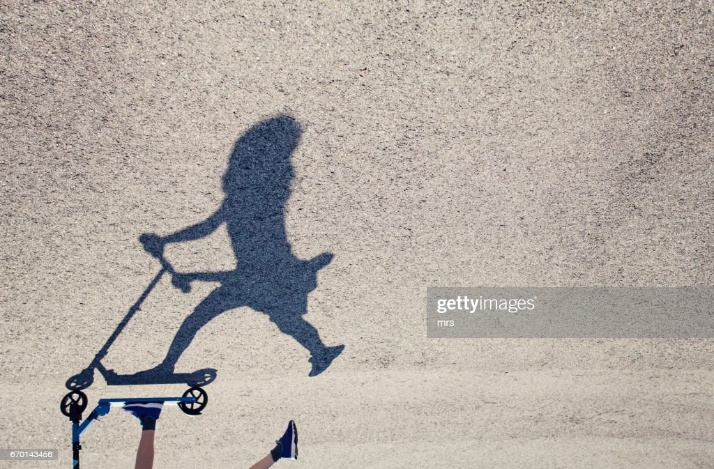 Girl riding her push scooter : Stock-Foto
