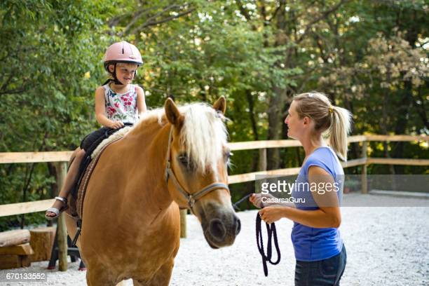 Girl Riding Horse In Paddock With Trainer Assisting