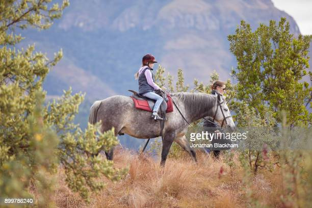 Girl riding horse in rural setting, mother walking by their side