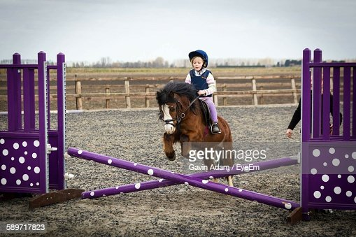 Girl Riding Horse On Field