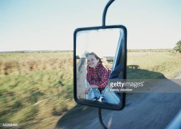 Girl (7-9) riding in back of pickup truck (blurred motion)