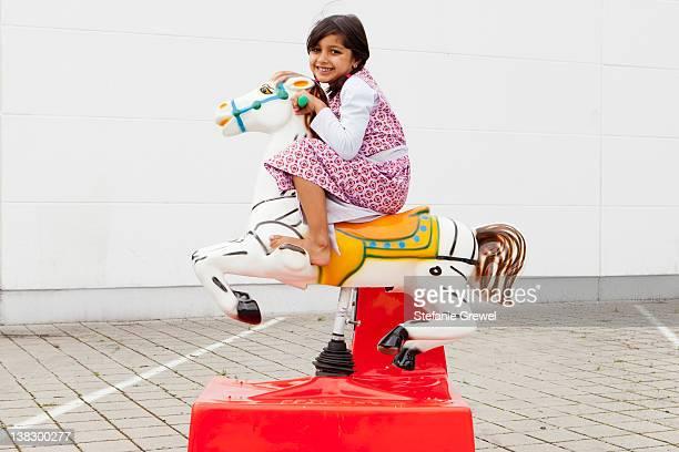 girl riding mechanical horse outdoors - stefanie grewel stock-fotos und bilder