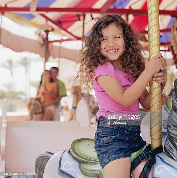 Girl (3-5) riding on carousel, smiling, portrait