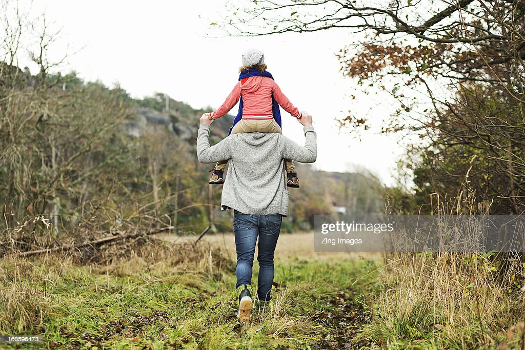 Girl riding on father's shoulders : Stock Photo