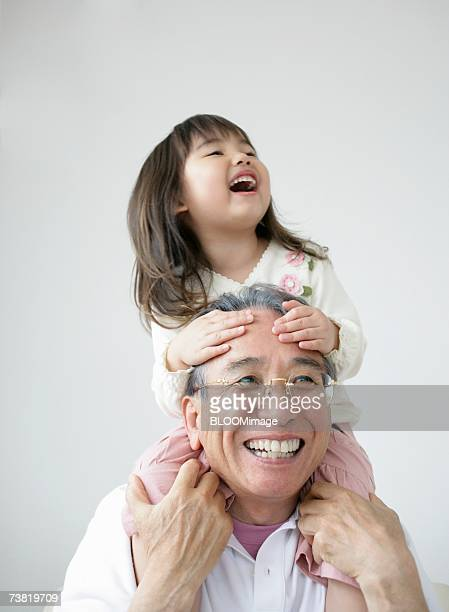 girl riding on grandfather's shoulders - carrying a person on shoulders stock photos and pictures