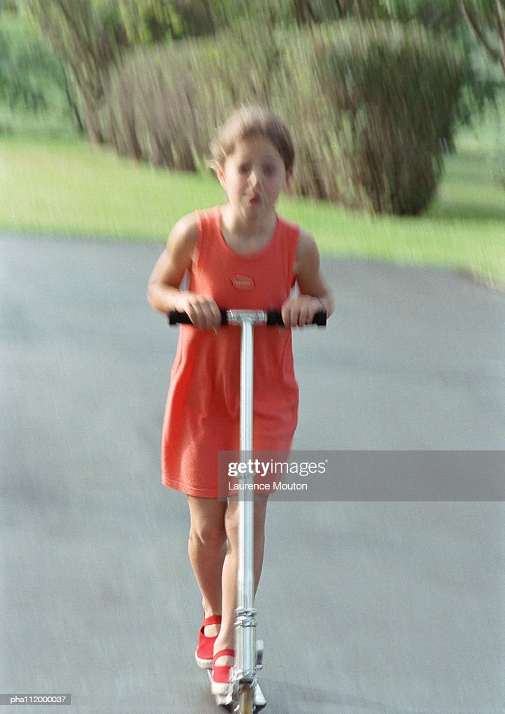 Girl riding scooter, blurred motion : Stockfoto