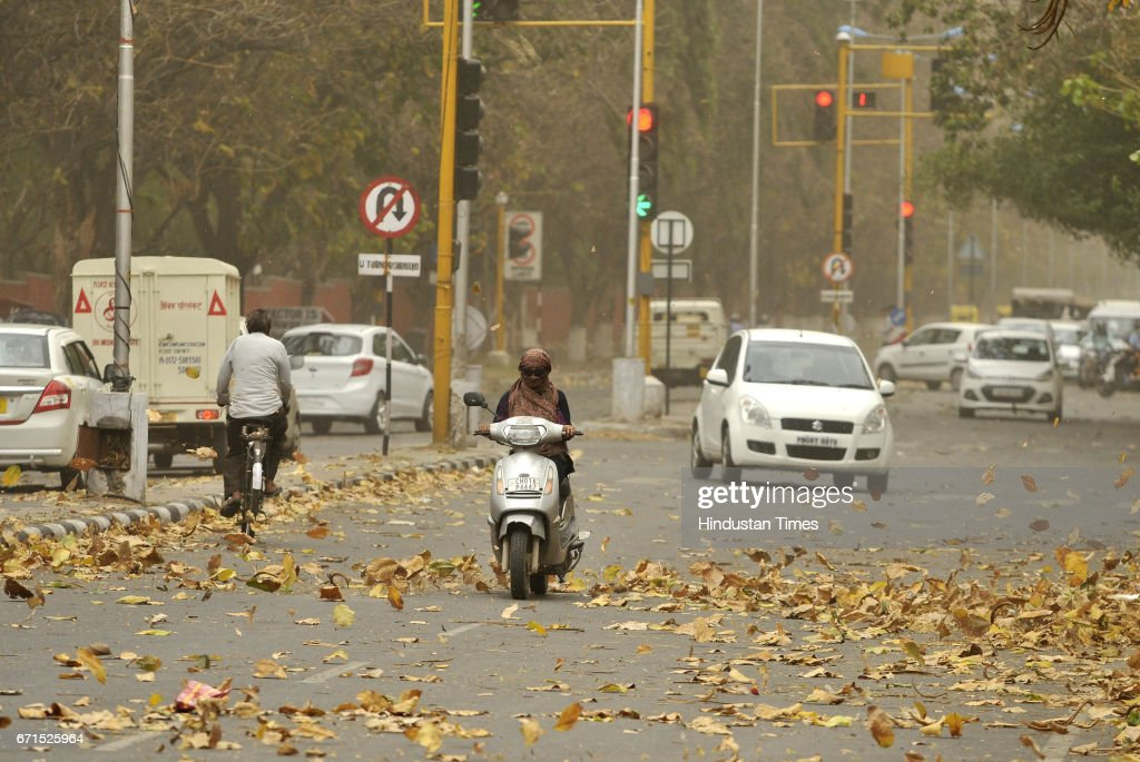 A girl riding scooty through the dust storm and strong winds on April 22 2017 in Chandigarh India The storm led to trees falling in some areas power..