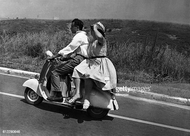 Girl riding sidesaddle on a scooter during a trip in the Italian countryside. June 1962 P04732