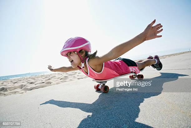 Girl riding skateboard at beach