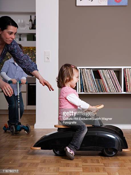 Girl riding toy car in living room
