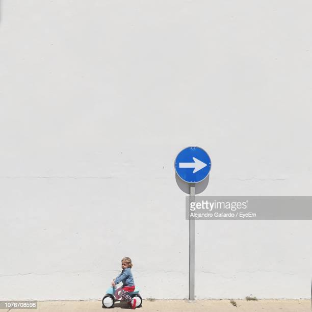 girl riding tricycle against arrow symbol by wall - segnaletica stradale foto e immagini stock
