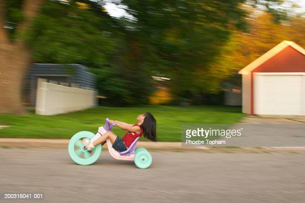 Girl (3-5) riding tricycle, side view, summer (blurred motion)