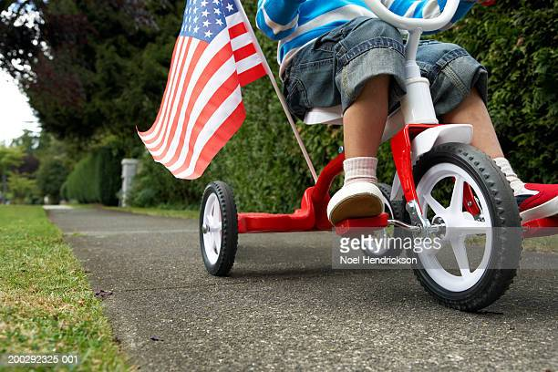 Girl (3-5 years) riding tricycle with USA flag along path, low section