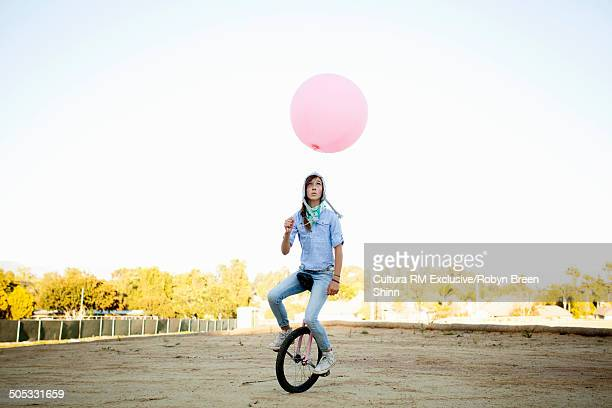 Girl riding unicycle, holding large pink balloon