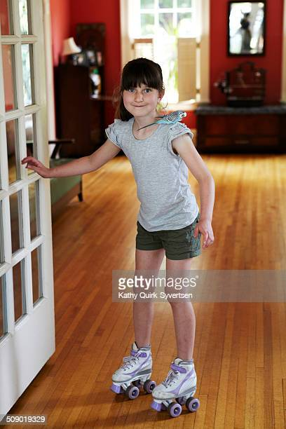 Girl roller skating in living room with pet bird