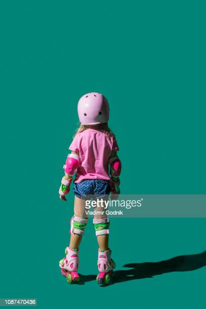 girl roller skating on green background - protective sportswear stock pictures, royalty-free photos & images