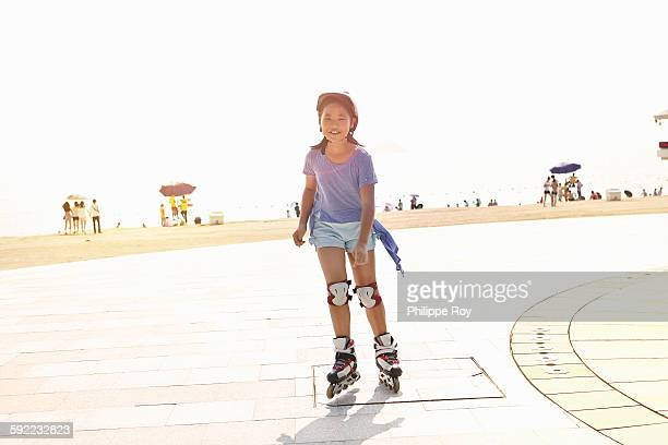 Girl rollerblading at beach, Zhuhai, Guangdong, China
