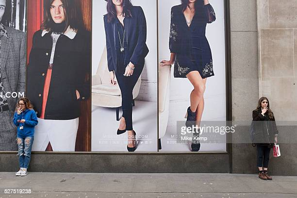 Girl rolling and smoking a cigarette while standing beside some large scale advertising pictures outside a fashion store London UK