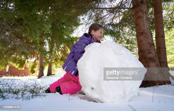 girl rolling huge snowball to make snowman. day is beautiful and sunny but cold so they wears warm clothes, romania. - snowman stock pictures, royalty-free photos & images
