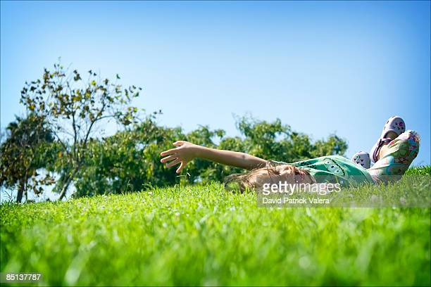 girl rolling in grass down a hill - de rola imagens e fotografias de stock