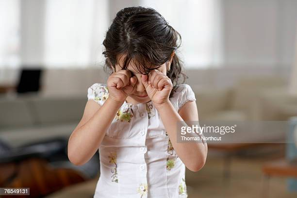 Girl (4-6) rubbing eyes, crying