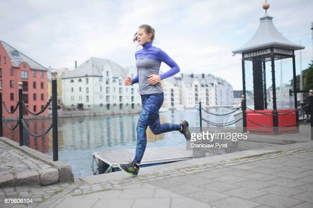 Girl running along water canal , ALesund city, Norway