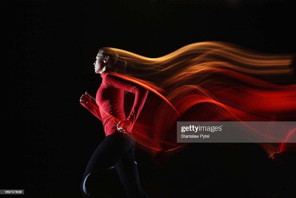 Girl running and leaving light streaks : Bildbanksbilder