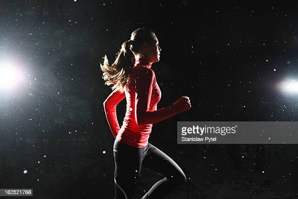 a girl running at night surrounded by snowflakes - lust girl stock photos and pictures