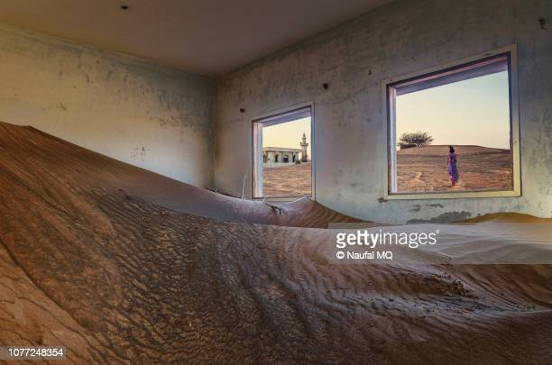 girl running away from a ruined house in desert of sharjah - emirate of sharjah stock pictures, royalty-free photos & images