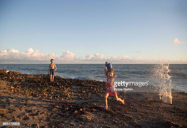girl running away from splashing wave on beach, blowing rocks preserve, jupiter island, florida, usa - blowing rocks preserve stock photos and pictures