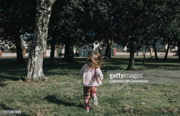 girl running away on grassy area - distant stock pictures, royalty-free photos & images